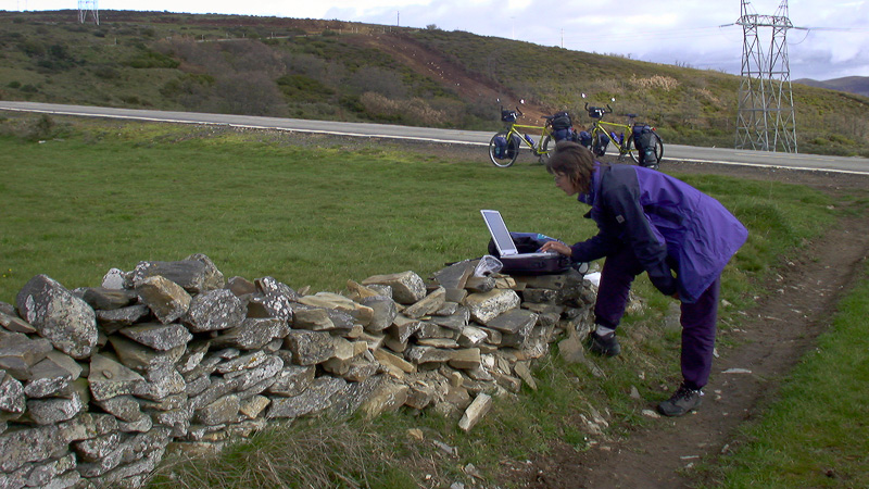 Beate Steger lädt auf einer Mauer auf dem Jakobsweg Bilder von der Digitalkamera auf den Laptop