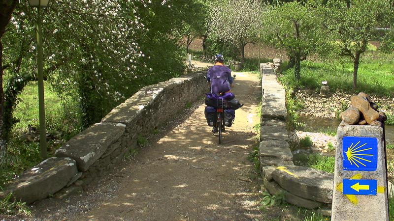 Carol Streeter radelt über eine alte Brücke auf dem Jakobsweg