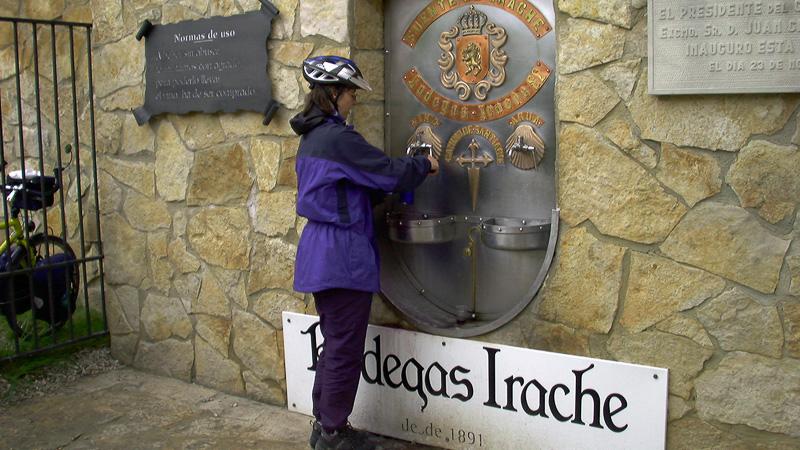 Beate Steger in voller Montur beim Abfüllen des kostenlosen Rotweins für die Pilger