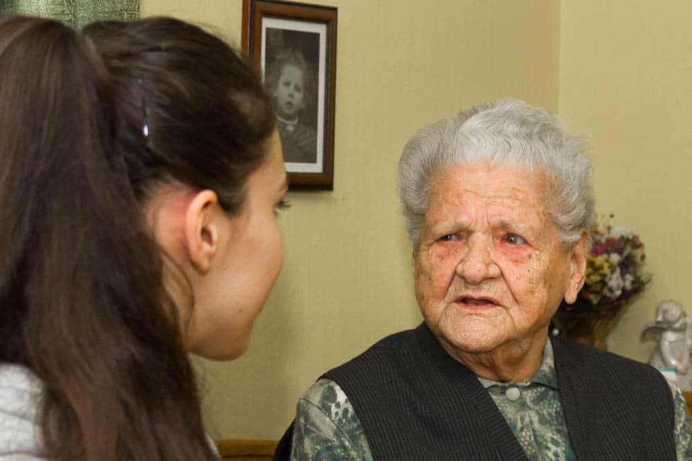 eine alte Frau schaut ein junges Mädchen intensiv an