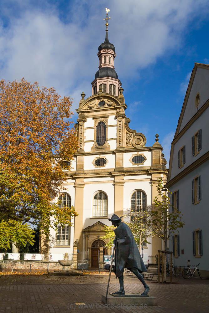 Die bronzene Pilgerstatue mit Pilgerstab und Pilgerhut und im Hintergrund die Kirche